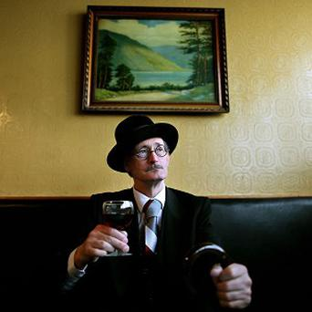 A James Joyce impersonator enjoys a drink in Dublin