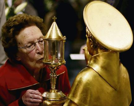 A woman honours the statue holding the relics after queueing along with hundreds of others at the church in Fairview yesterday