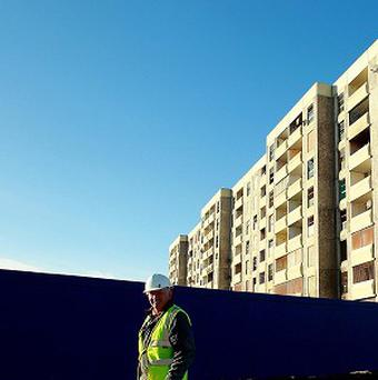 A construction worker passes a tower block, due to be demolished as part of the Ballymun Regeneration project