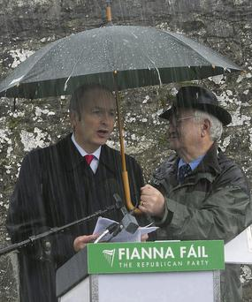 Fianna Fail leader Micheal Martin is kept dry by Sean Sherwin during his oration