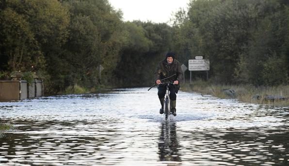 Farmer Jerry Kelliher making his way home through floods after tending his cattle at Glenflesk, Killarney, Co Kerry, yesterday