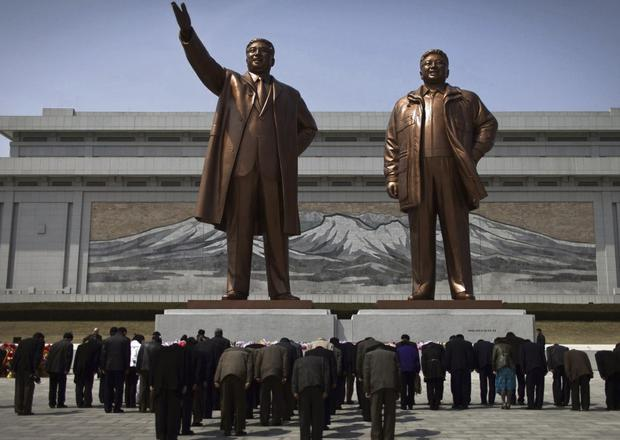 DEAR LEADERS: North Koreans bow down earlier this year to statues of the country's late leaders Kim Il Sung, left, and Kim Jong Il in Pyongyang