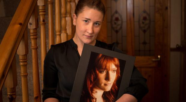 Sharon Hennessy holding a picture of her late twin Sister Michelle at her home yesterday evening