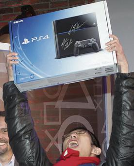 A shopper celebrates with his new PlayStation console in New York on launch day last year