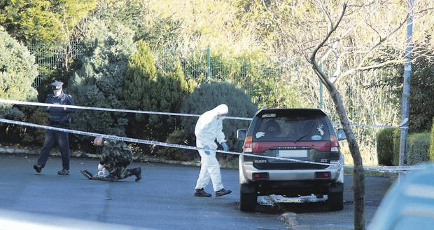Garda forensic experts examine the scene after a bomb exploded under the car of Alan Coyle