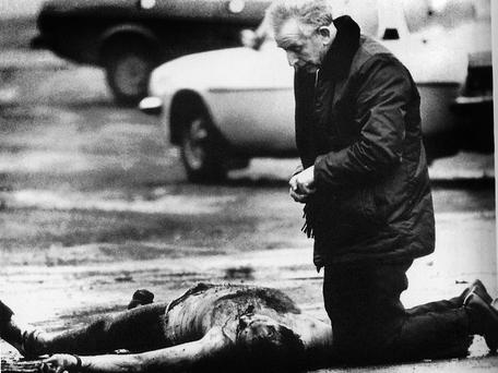 MAN OF GOD: Fr Reid beside the body of one of two British soldiers killed by the IRA at a republican funeral in Belfast