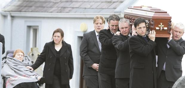 The remains of Mr Gilmartin are carried by family members as his wheelchair-bound wife, Vera, looks on.
