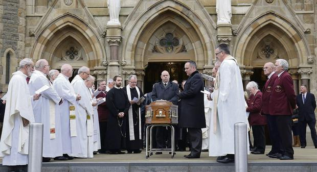 The coffin of Fr Alec Reid leaves the church.