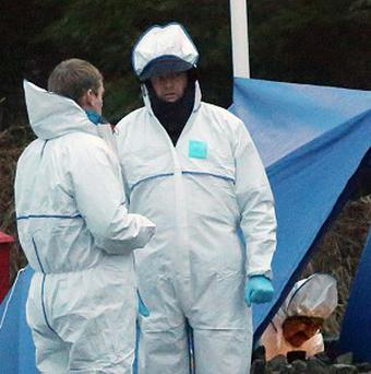 Deputy State Pathologist Dr Khalid Jabbar (pictured here on the right at a crime scene) has resigned from his post