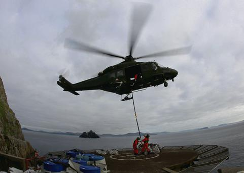 An Air Corps helicopter delivering stone slabs for repairs to the walls on the road up to Skellig Michael lighthouse.