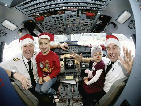 Aer Lingus Regional Captain Mark Bell (left) and First Officer Derek Creighton with Pierce Duggan (6) and Merryn Lacey (4) in the cockpit of the 'Santa Express' aircraft in Dublin Airport.