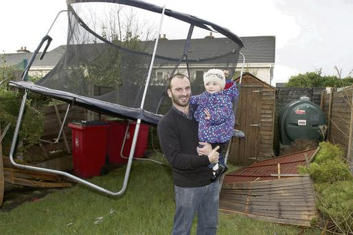 Malachy Duggan and his daughter Easkey (2) woke to find a giant trampoline had been blown into their back garden by high winds in Knocknacarra, Galway.
