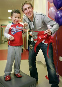 Temple Street patient Dylan Doyle (4), from Ballymun, helps Irish cyclist Dan Martin cut the ribbon to the revamped ward. Photo: Frank Mc Grath