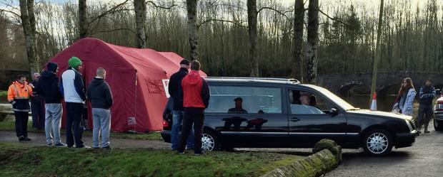 The body of student Jonny Byrne is taken away by a hearse after it was taken from the River Barrow, near Milford Bridge, Co Carlow, as family and friends look on.