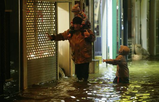 A man with two children make their way through flood water in Cork city.