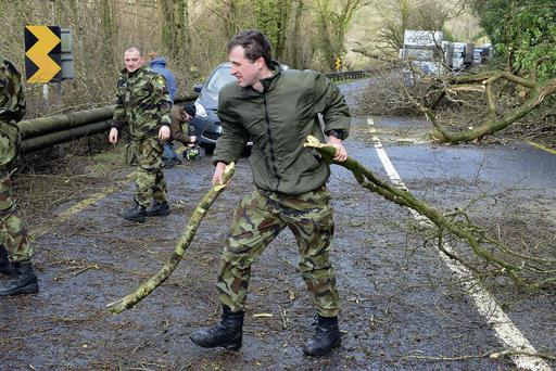 Troops clear a path for traffic on the main Cork Bandon road where volunteers council workers Gardaí and Members of the Defence forces from Collins barracks removed a number of fallen trees that Blocked the main N71 Road at Innishannon. Picture Denis Boyle