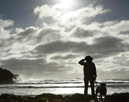 Clodagh Redden (Glandore) is pictured with her dog 'Bella' watching the huge waves as they batter Warren Strand Beach, West Cork
