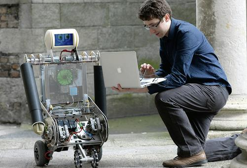 Trinity College student Michael Cullinan with 'Robbie the Robot', developed for Cork teenager Joanne O'Riordan. Caroline Quinn