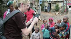 Jane Last from the 'Irish Independent' with children in Imizamo Yethu Township. Photo: Niall Carson
