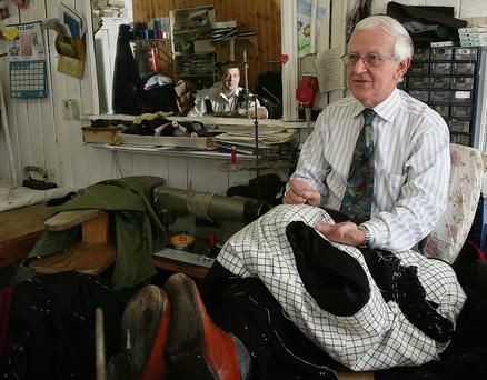 Tailor Michael Johnson works in his Tullow shop, with his son Robin in the background.