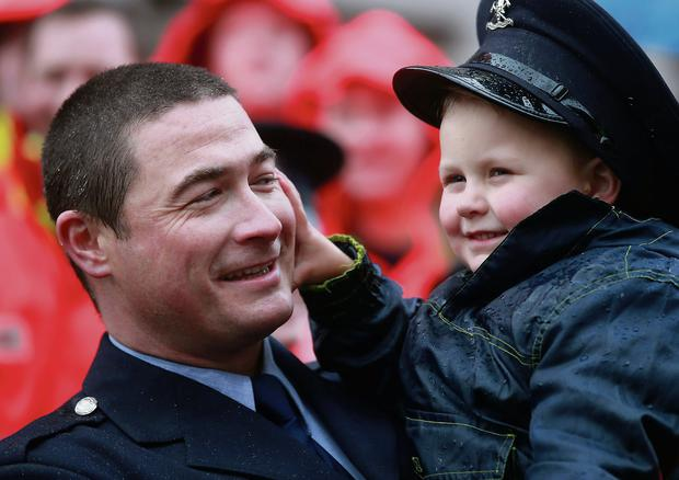 Fireman Neil McCabe and his son Eoghan, aged three, at the march in Dublin city centre. Picture Arthur Carron.