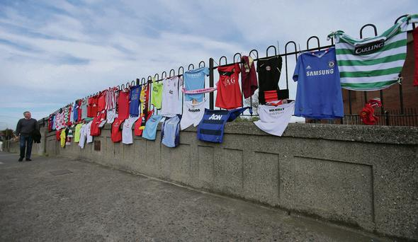 A passerby looks at football jerseys on the bridge and, inset, the defaced plaque on Monday.