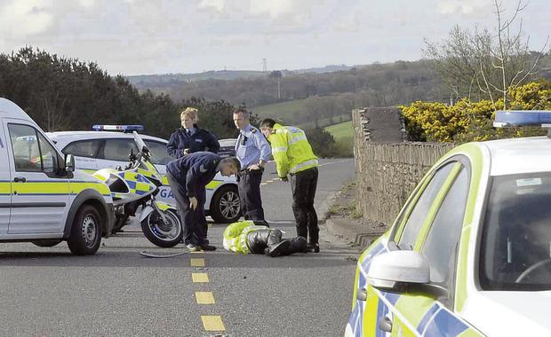 The injured garda lies in the road surrounded by colleagues.