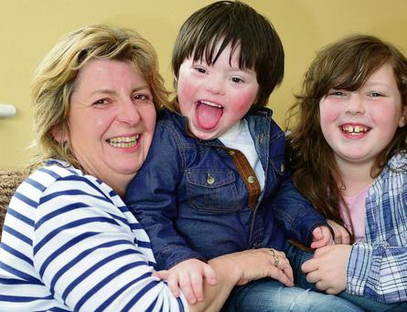 Ben Hughes (4), from Co Meath, who has Down Syndrome and has had his medical card taken from him. Pictured with Ben is his mum Amanda and his sister Amie (9). Picture: Ciara Wilkinson