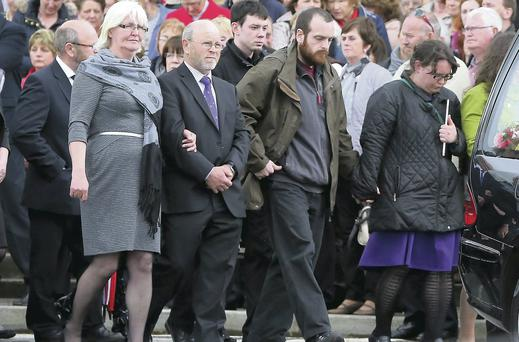 Grief-stricken parents Margo and Peter, left, link one another, at the funeral of daughter Mairead Moran, at Kilmoganny, Co Kilkenny, yesterday. Patrick Browne