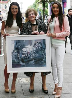 Mary Keane and grand-daughters Laura and Maggie hold the portrait of the late playwright.
