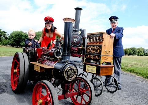FULL STEAM AHEAD: At the launch of the 50th National Steam Rally were Clifton Flewitt from the narrow-gauge railway, model Michele Mc Grath, and 3-year old Charlie Glynn. Charlie is at the controls of a engine that was used on a farm in Carlow before it went to Ballon creamery in the 1960s; the engine steam was used to sterilise milk bottles. This is the engine's first time at Stradbally as it has just been restored by the Glynns from Co Carlow. Photo: Tony Maxwell