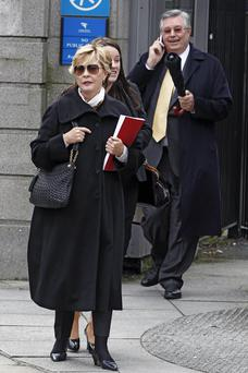 Leona (Lee) Flynn (L), wearing sunglasses, of Palm Beach, Florida, leaving court. Her husband, John Flynn, is seen also.