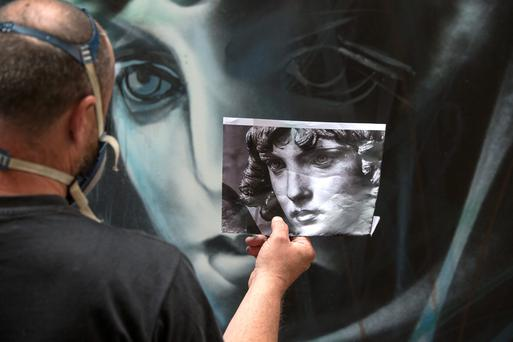 A street and stencil artist creates a painting for the opening of outvision Ireland's first open air gallery at Crampton Court, Temple Bar, Dublin