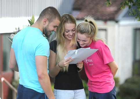 Lauren Vesey, 18, a student from St Raphaela's Secondary School in Stillorgan looks at her Leaving cert results with friends. Picture credit; Damien Eagers