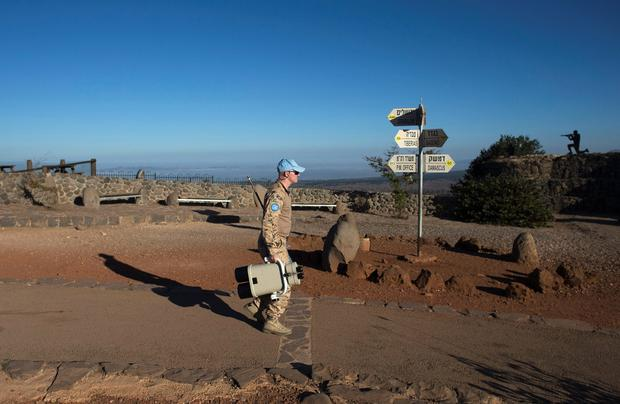 A member of the U.N. Disengagement Observer Force (UNDOF) carries binoculars at an observation post in the Golan Heights that overlooks the Syrian side of the Qunietra crossing