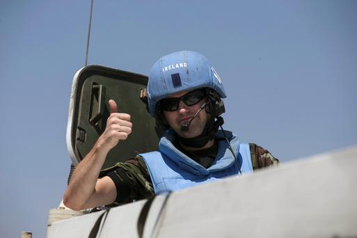 An Irish member of the United Nations Disengagement Observer Force (UNDOF) gestures from an armoured personnel carrier (APC) in the Israeli-occupied Golan Heights before crossing into Syria August 31, 2014.