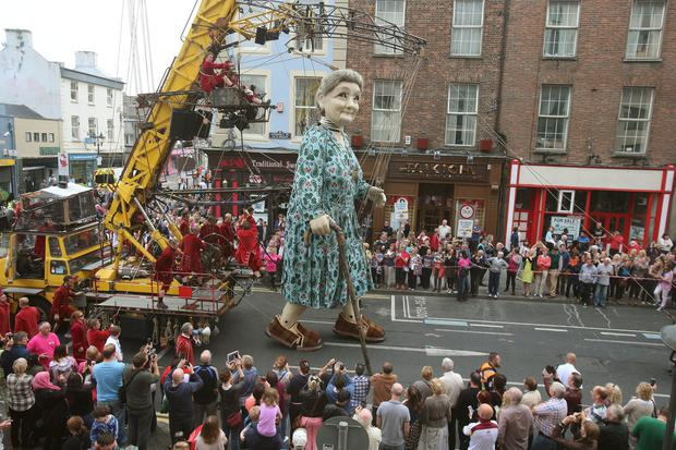 Crowds watch as performers from the French arts group Royal de Luxe take to the streets of Limerick with their giant grandmother parade as part of this years city of culture celebrations. Photo: PA