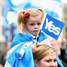 A young girl holds a flag at a 'Yes' campaign rally in Glasgow, Scotland