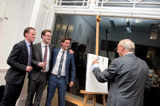 Pictured (LtoR) Paul-Emmet, Nicholas and William Costelloe pose as their father Paul Costelloe sketches them at their joint exhibition Family Ties at the Sol Art Gallery on Dawson street.