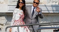 U.S. actor George Clooney and his wife Amal Alamuddin leave the seven-star hotel Aman Canal Grande Venice in Venice