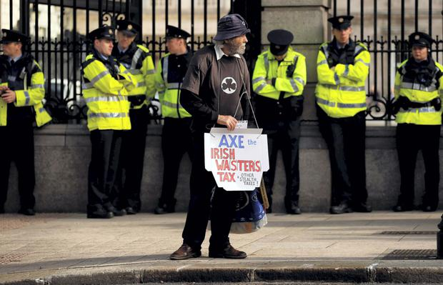 Winter of discontent: A man protests at the gates of Leinster House during the announcement of the 2015 Budget. Now that the water charges debacle seems to be at an end, the Government is keen to remind us how great their Budget was. Photo: Reuters.