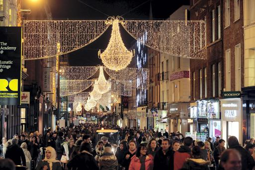 Shoppers walk under the Christmas lights on Grafton Street in Dublin