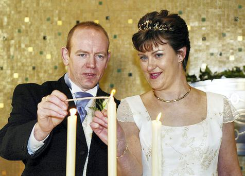 Pearse McAuley and Pauline Tully light a candle after their wedding in Kilnaleck, Co Cavan, in 2003. Photo: John McAviney