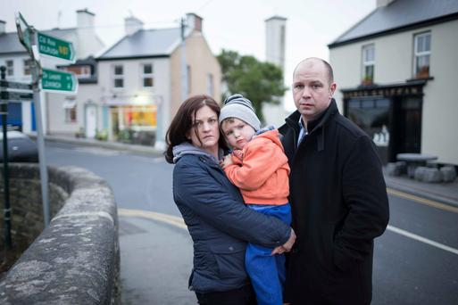 John and Sheena Clancy with son Jamie (4) whose home and business (behind them in photo) in Ennistymon, Co Clare, could be bulldozed. Photo: Eamon Ward