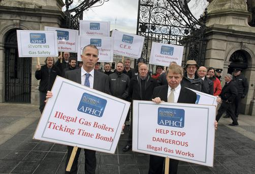 Jimmy Egan,Secretary (left) and Sean Giffney, Chairman and members of the Association of Plumbing and Heating Contractors Ireland (APHCI) demonstrate before the Joint Oireachtas Committee for Communications, Energy and Natural Resources meeting at Leinster House yesterday. Picture: Tom Burke
