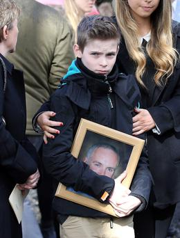 Oisin Drury (10) holds a pictured of his father at the funeral service for Paul Drury at Rathmichael Parish Church in Dublin yesterday. Photo: Frank McGrath