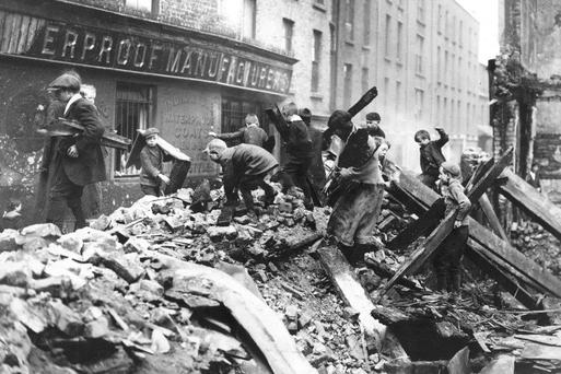 Poor children of Dublin collect firewood from the rubble of buildings destroyed during the Rising