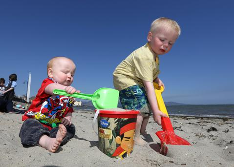 Kealan McNally-Matthews (4) from Dundalk gets a little help from his brother Tiernan (1) to make a sand castle on the beach in Blackrock, Co Louth. Photo: Frank McGrath