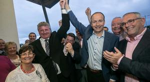 Fianna Fáil leader Micheál Martin celebrates with the party's by-election candidate Bobby Aylward on his victory in the Carlow-Kilkenny by-election