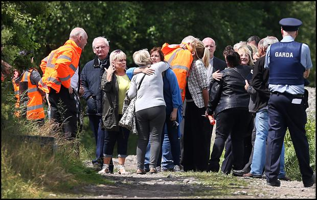 Family members comfort each other after undertakers remove the bodies of the dead men at the scene at where the human remains were found in Coghalstown, Co Meath